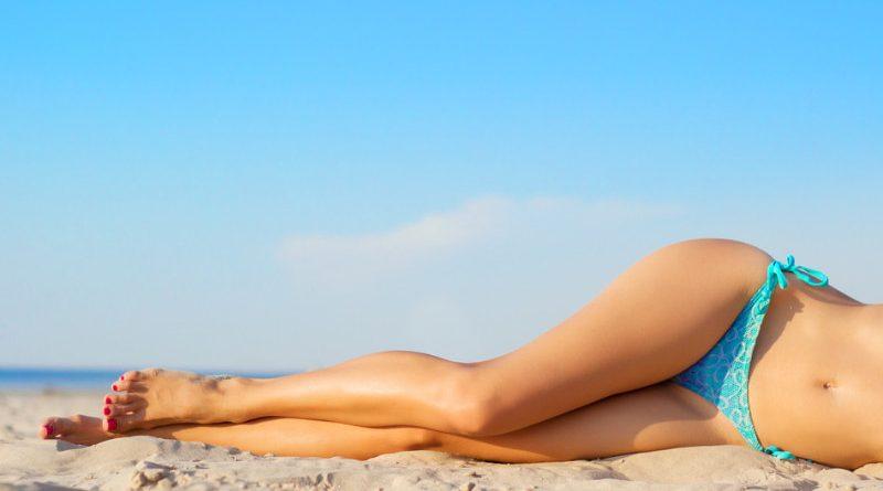 lady in bikini laying on the sand