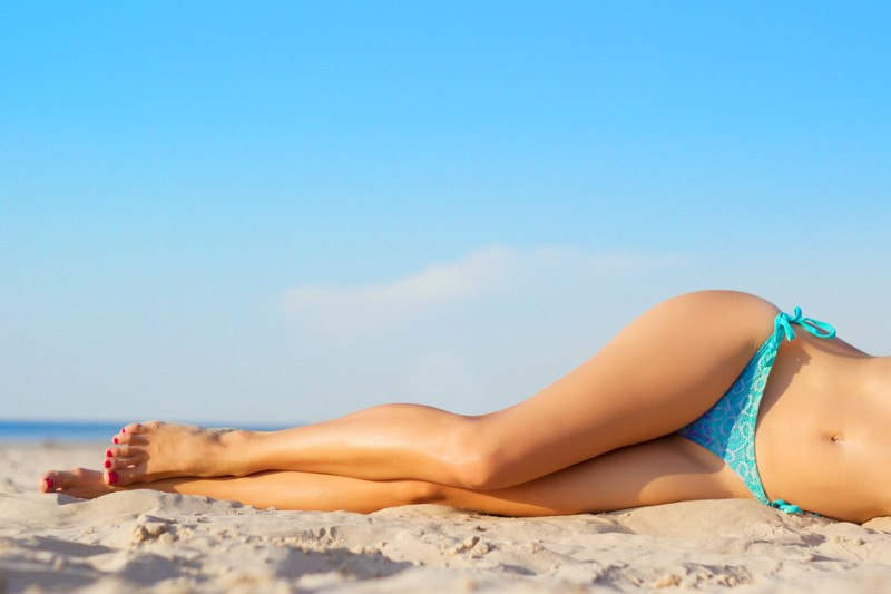 lady in bikini laying on the sand