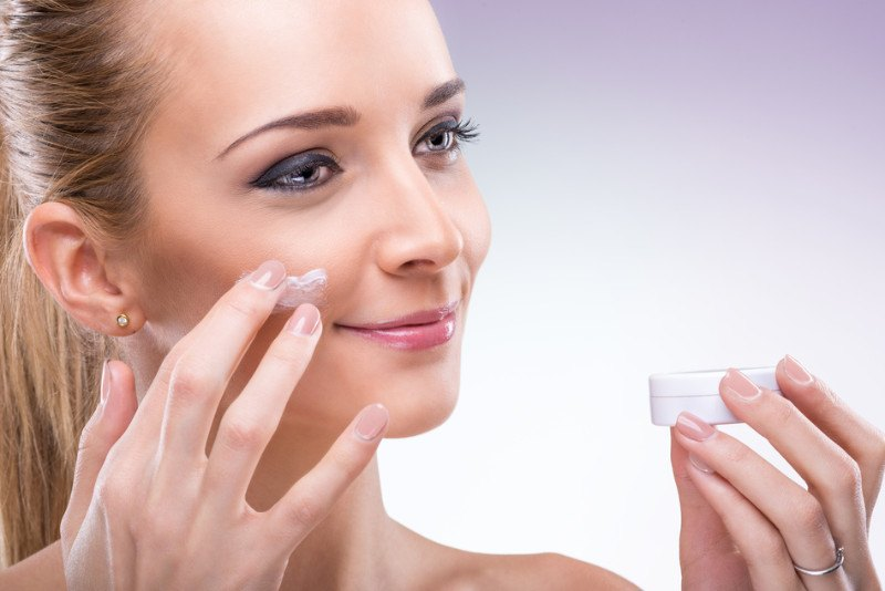 woman applying moisturizer