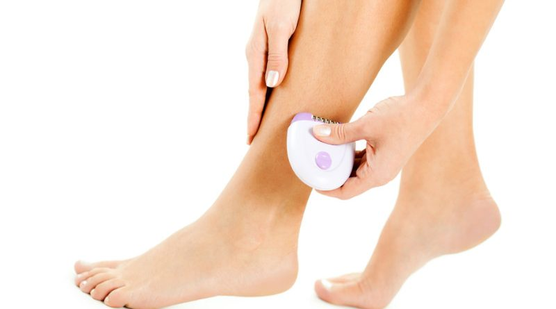 woman using electric razor on legs
