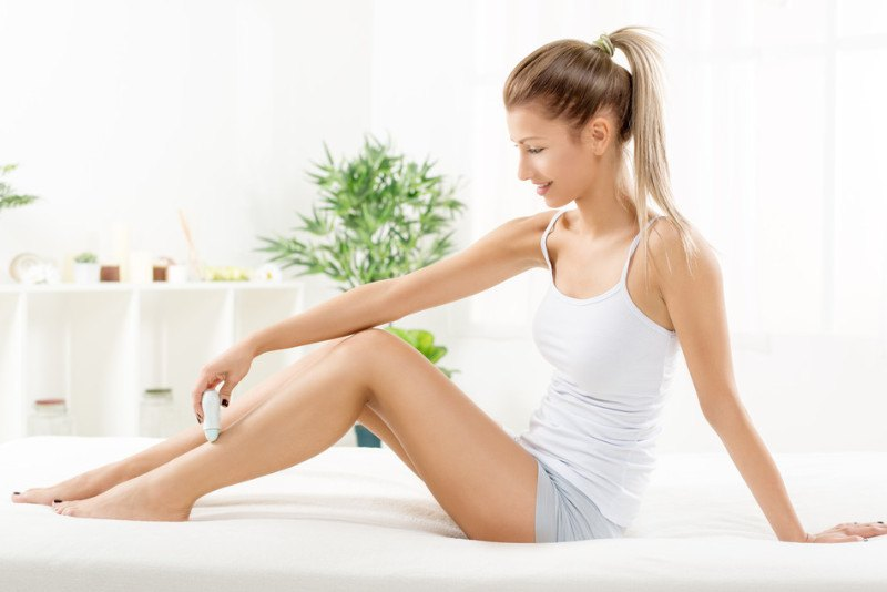 woman using epilator on legs