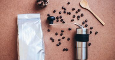 coffee grinder, beans, spoon and bag of grinds