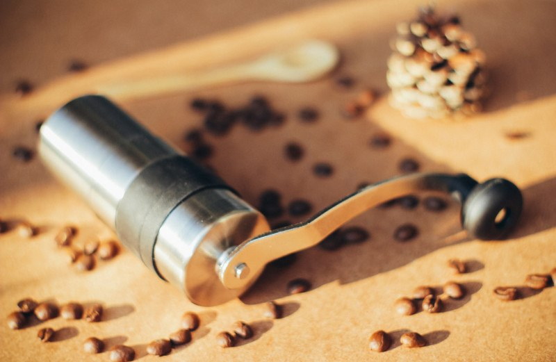 manual grinder surrounded by coffee beans