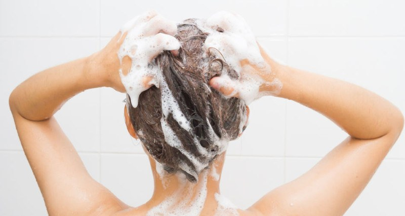 A woman in a white shower shampooing her hair.