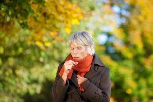 woman coughing in a park