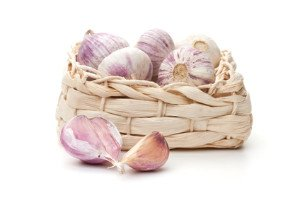 A straw basket full of garlic cloves.