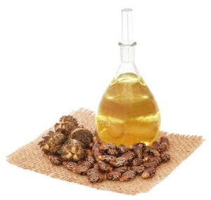 A jar of castor oil and some castor beans sitting on a piece of hessian.