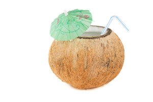 A coconut full of coconut water with a straw and paper umbrella.