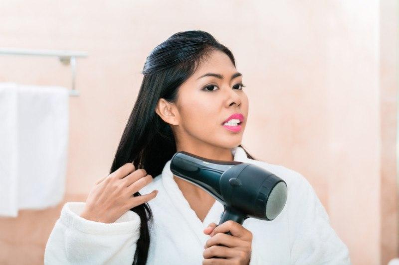 asian-woman-in-hotel-bathroom-drying-hair