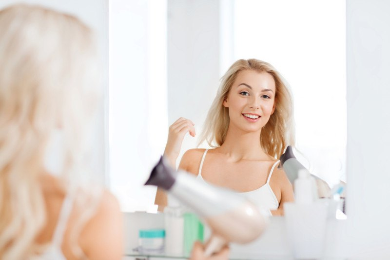 happy-young-woman-with-fan-drying-fine-hair-at-bathroom