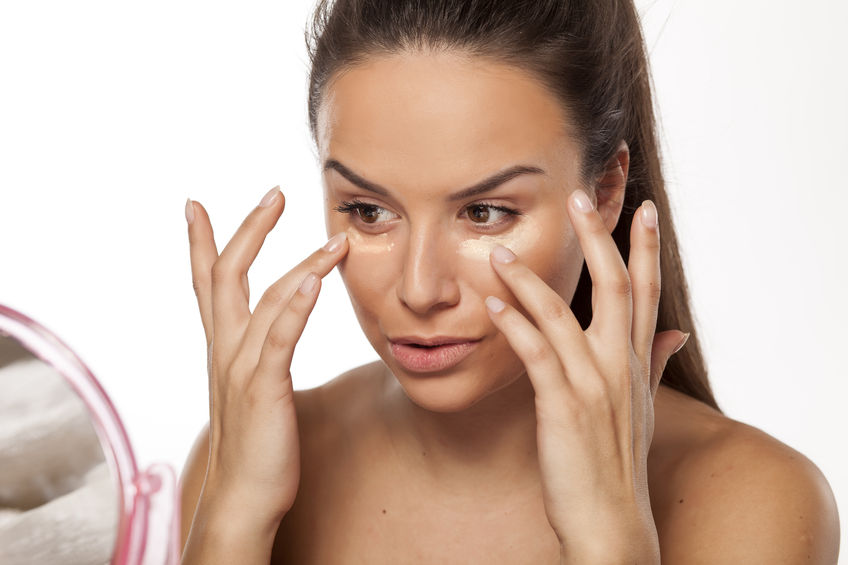 woman applying makeup primer to her face