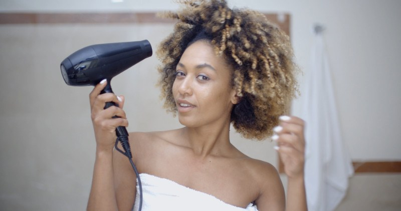 woman-with-curly-hair-drying-her-hair-with-hairdryer