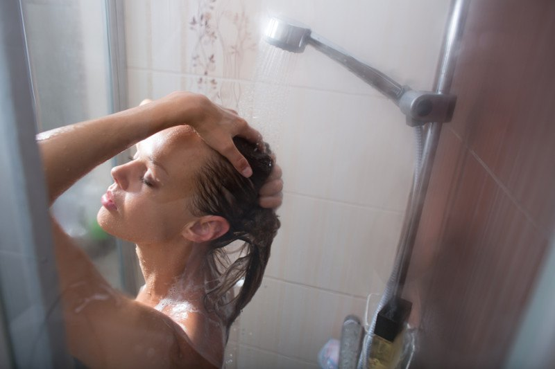 young-woman-washing-her-hair-with-shampoo