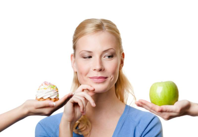 young-woman-makes-a-choice-between-cake-and-apple